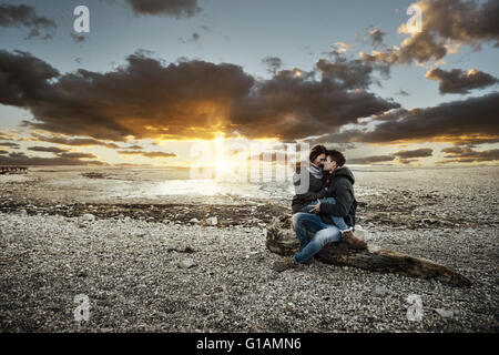Young couple having a romantic date at the lake, they are hugging and sitting on a trunk on the beach, love and - Stock Photo