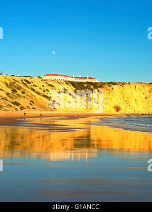 People on the ocean beach at sunset. Full moon in the sky.  Portugal - Stock Photo