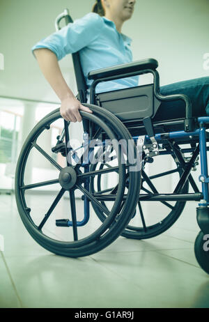 Young woman in wheelchair hand pushing on wheel close up, disability and handicap concept - Stock Photo