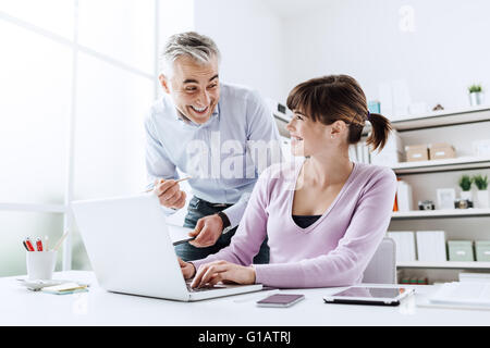 Cheerful business people in the office, they are working together and smiling, the woman is typing on a laptop - Stock Photo