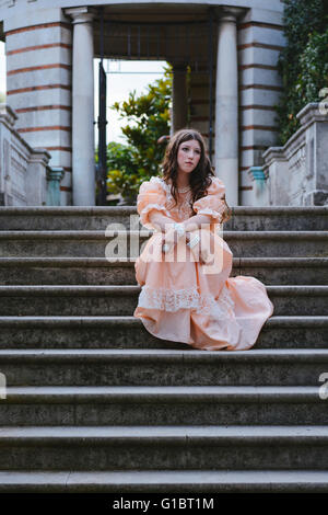 Thoughtful Victorian woman is sitting on the stairs - Stock Photo