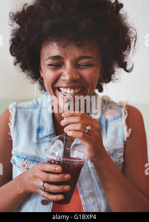 Close up portrait of cheerful young woman drinking fresh fruit juice and smiling. Happy young african female model - Stock Photo