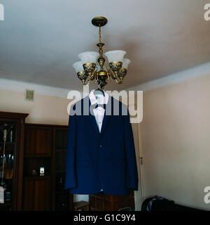 Elegant stylish blue wedding suit hanging on chandelier in hotel room - Stock Photo