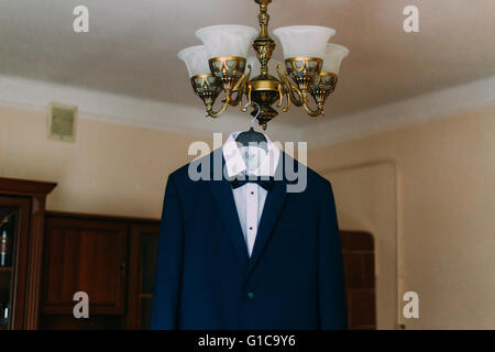 Groom stylish blue wedding suit hanging on chandelier in hotel room - Stock Photo