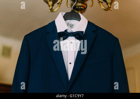 Elegant stylish blue wedding suit hanging on chandelier in hotel room close-up - Stock Photo