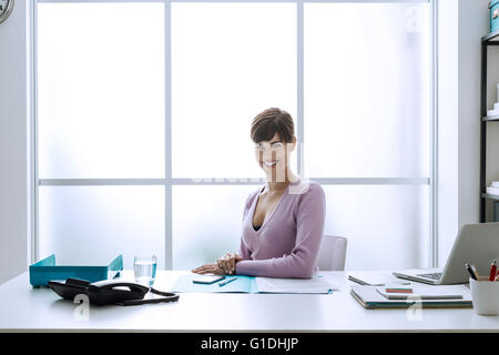 Confident smiling young businesswoman in her office, she is looking at camera and sitting at desk - Stock Photo