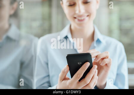 Beautiful smiling young woman using a smart phone, leaning on a window and reflecting on glass - Stock Photo