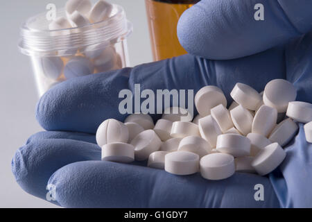 blue gloved hand holding white pills with medication bottles in background - Stockfoto
