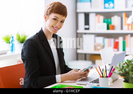 Successful confident businesswoman in her office using a smart phone, she is texting and using a mobile app - Stock Photo