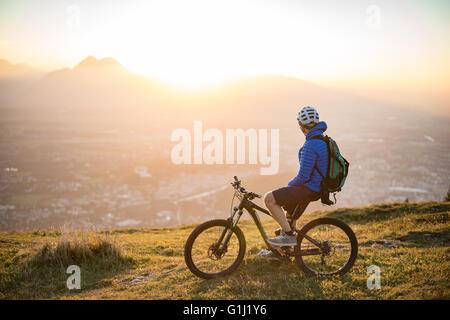 Man on mountain bike looking at sunset view, Salzburg, Austria - Stock Photo
