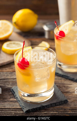 Homemade Whiskey Sour Cocktail Drink with a Cherry Lemon - Stock Photo