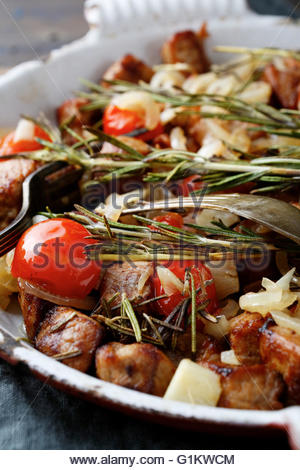 Closeup of Roasted Pork Meat with tomatoes and spices on frying pan - Stock Photo