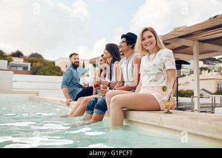 Portrait of happy young woman sitting by the pool with her friends partying. Young people relaxing by the swimming - Stock Photo