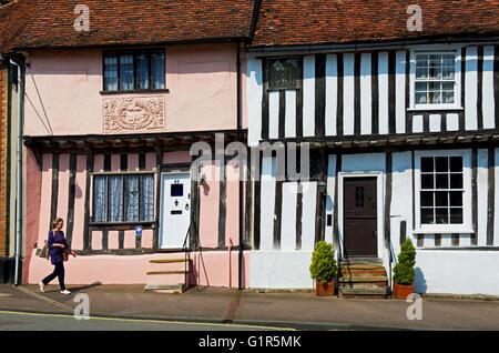 Woman walking past half-timbered houses in Lavenham, Suffolk, England UK - Stock Photo
