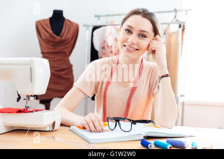 Portrait of cheerful beautiful young woman seamstress working in sewing workshop - Stock Photo