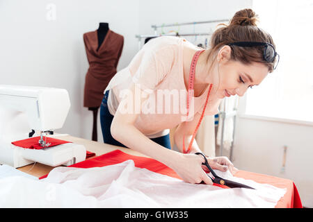Beautiful focused young woman fashion designer cutting white fabric in studio - Stock Photo
