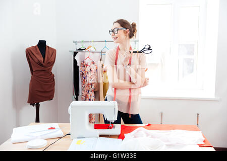 Cheerful attractive young woman seamstress with scissors standing and smilig in design studio - Stock Photo