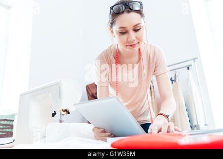 Serious beautiful young woman seamstress with tablet working and thinking in workshop - Stock Photo