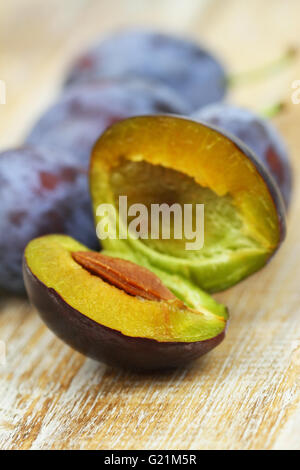 Cross section of a plum on wooden surface, closeup - Stock Photo