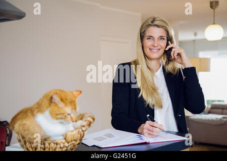 A middle aged woman wearing a suit happily talks on the phone while her pet cat sits atop the counter beside her - Stock Photo