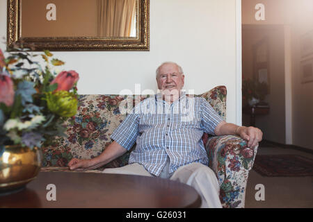 Indoor shot of happy senior man sitting relaxed on a couch at old age home. He is looking at camera and smiling. - Stock Photo