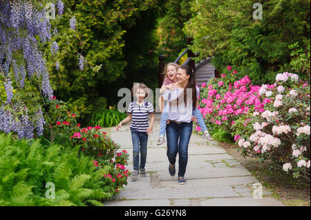 On a summer day, mother came with children in a blooming Japanese garden. They walk in the fresh air. The daughter - Stock Photo