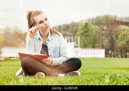 Pensive serious woman sitting outside on grass and writing in her diary with copy space - Stock Photo