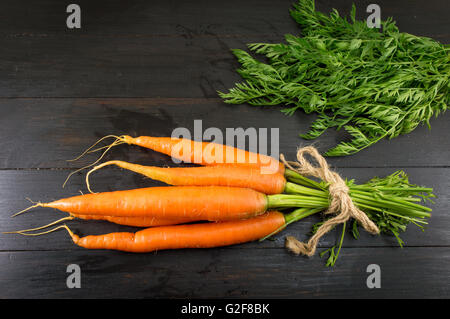 Fresh carrot bouquet on a dark wooden board - Stock Photo
