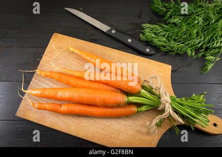Fresh carrot bouquet on a dark wooden board - Stockfoto