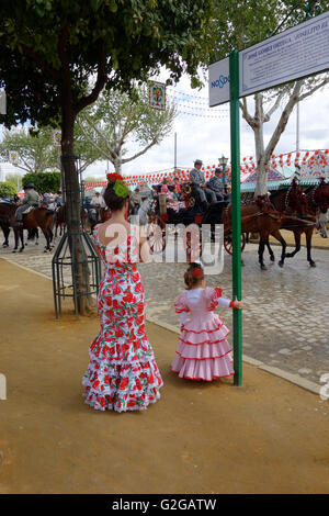 watching the procession Feria di Abril  Seville Sevilla Andalucia Spain mother and daughter in traditional dress - Stock Photo