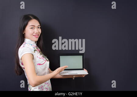 Young asian woman holding a laptop wearing chinese dress - Stock Photo