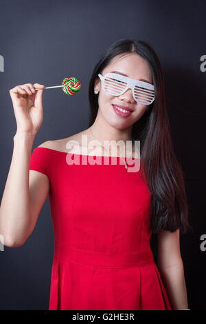 Beautiful woman holding a lollipop while wearing red dress - Stock Photo