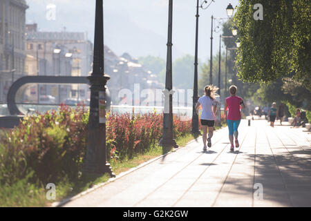 two middle aged female friends jogging have morning workout with sunrise in background - Stock Photo