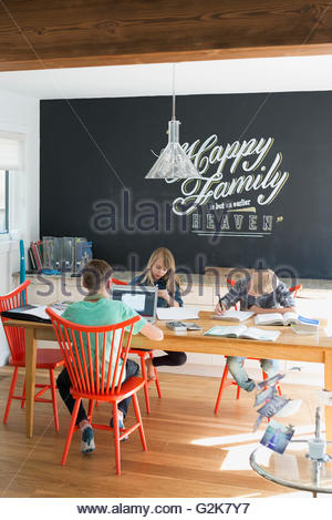 Brothers and sister doing homework at dining table - Stock Photo