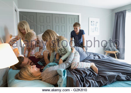 Playful children in pajamas tackling parents in bed - Stock Photo