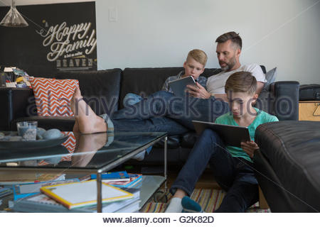 Father and sons relaxing with digital tablets in living room - Stock Photo
