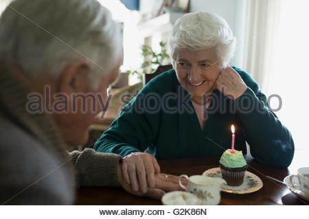 Affectionate senior couple celebrating birthday with cupcake and tea - Stock Photo