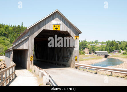 The historic wooden bridge with another the same bridge in a background built over Vaughan Creek in St.Martins (Canada). - Stock Photo