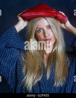 Zoe Mcconnal poking her tongue out with a hot water bottle on her head - Stockfoto