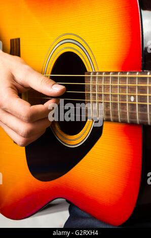 closeup of hands of a musician playing acoustic guitar ...