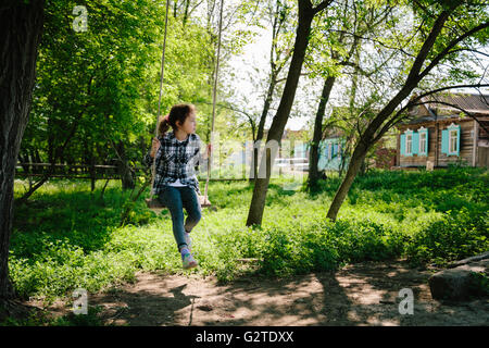 girl riding on a swing in the village - Stockfoto