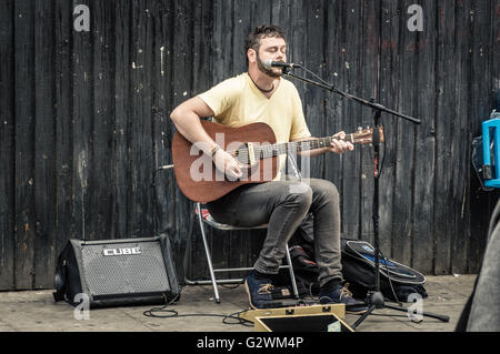 LONDON, UK - AUGUST 20, 2015: Street musician plays acoustic guitar near at Camden Town Market. - Stock Photo