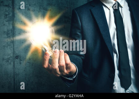 Business creativity and vision concept with elegant adult businessman holding bright light bulb as metaphor of new - Stock Photo