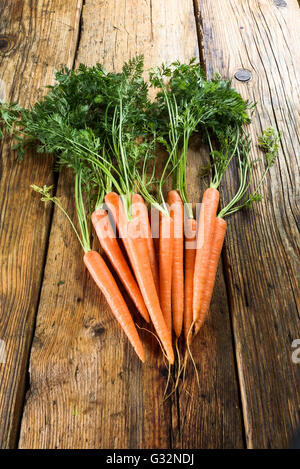 Juicy bunch of carrots on a rustic wooden table. - Stockfoto