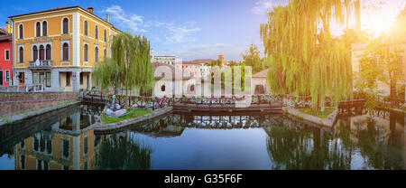 Idllyic view of famous Mills on the Lemene river in the historic city center of Portogruaro in golden evening light, - Stock Photo