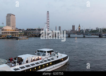 A cruiser sails up the River Thames as dusk falls, with Westminster in the distance beyond Hungerford Bridge - Stock Photo
