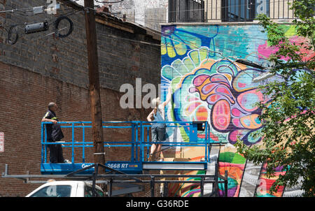 Female street artist at work on a mural on an elevated platform on Christopher Columbus Drive, Jersey City - Stock Photo