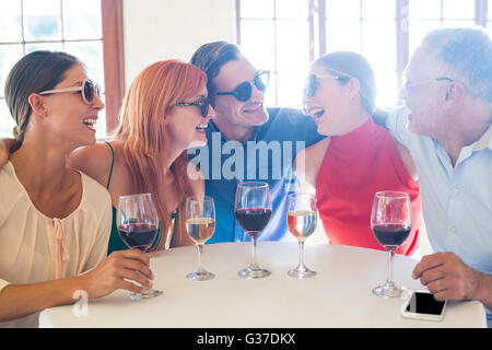 Group of friends in sunglasses laughing in restaurant - Stock Photo