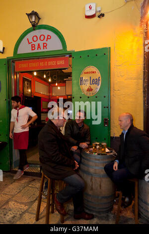 People drinking in the alleyway outside a retro bar in Strait Street in Valletta. - Stock Photo