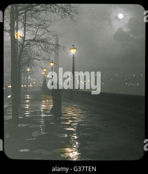 A woman walking along the  Embankment on a rainy night  with a full moon        Date: 1910 - Stockfoto